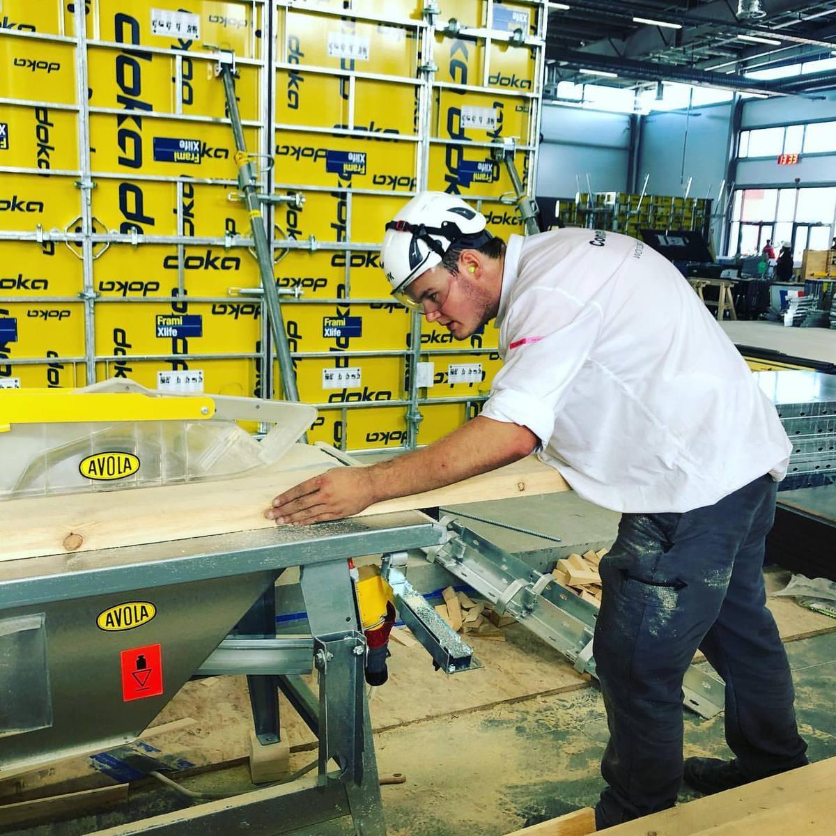 Stahlbetonbauer Niklas Berroth konzentriert sich voll und ganz auf die Säge, um den Balken exakt anzupassen.